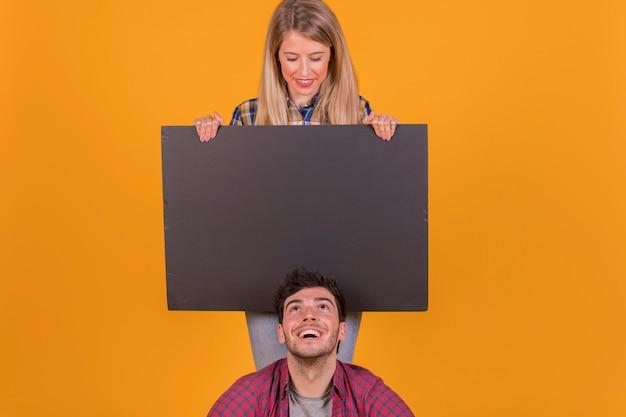 Hombre joven que mira el asimiento negro en blanco del cartel de su novia contra un fondo anaranjado Foto gratis