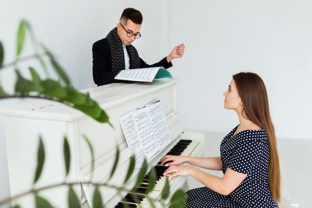 Hombre joven que mira la hoja musical que ayuda a la mujer que toca el piano Foto gratis