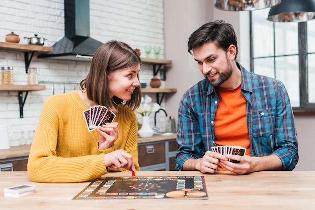 Hombre joven que mira a su esposa que juega el juego de mesa en el escritorio de madera Foto gratis