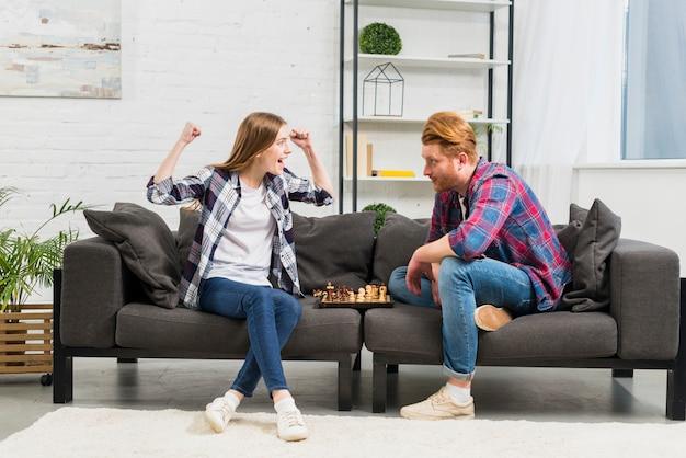 Hombre joven que mira a su novia que anima con éxito mientras que juega al ajedrez Foto gratis