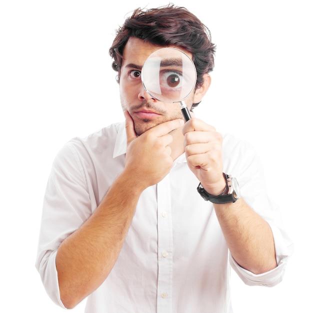 Hombre joven que mira a través de la lupa Foto Premium