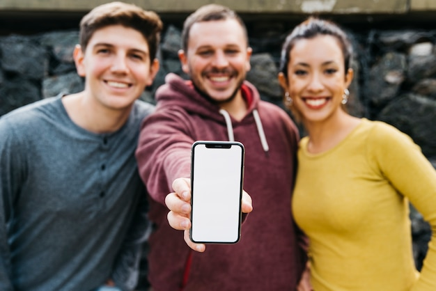 Hombre joven que muestra la pantalla vacía del teléfono inteligente mientras está de pie cerca de amigos multirraciales Foto gratis
