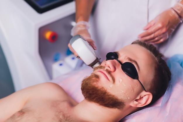 Hombre joven que recibe el tratamiento de depilación láser en el centro de belleza. Foto Premium