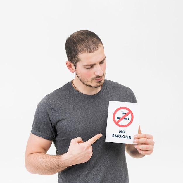 Hombre joven que señala su dedo hacia la muestra de no fumadores aislada en el contexto blanco Foto gratis