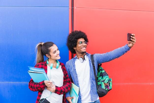Hombre joven que toma selfie con su novia sosteniendo libros en la mano en el teléfono móvil contra la pared roja y azul Foto gratis