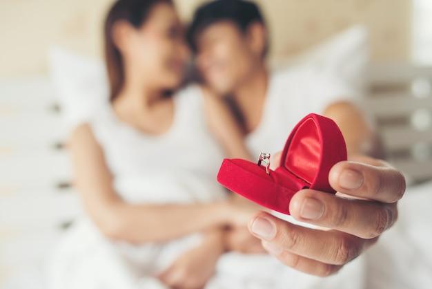 Hombre joven que trae caja de anillo para su novia en su casa Foto gratis
