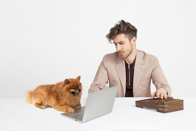Hombre joven que usa el ábaco ruso mientras que el perro del perro de pomerania se sienta cerca del cuaderno Foto Premium