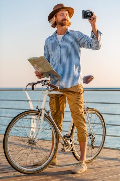 Hombre joven que viaja en bicicleta por el mar en las vacaciones de verano junto al mar al atardecer, sosteniendo el mapa de turismo tomando fotos en la cámara Foto gratis