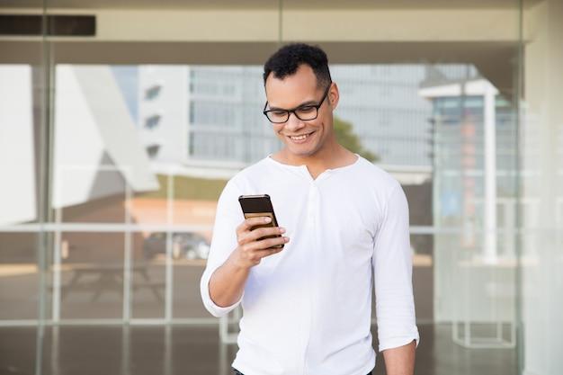Hombre joven de la raza mixta que manda un sms en el teléfono, sonriendo. vista frontal Foto gratis