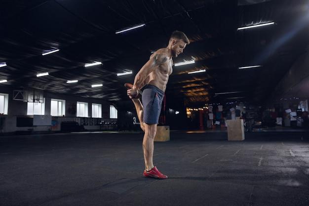 Hombre joven sano, atleta haciendo ejercicios, estiramiento en el gimnasio. solo modelo caucásico practicando duro, entrenando su cuerpo. concepto de estilo de vida saludable, deporte, fitness, culturismo, bienestar. Foto gratis