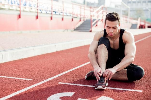Hombre joven sano sentado en la pista de atletismo atando su cordón Foto gratis