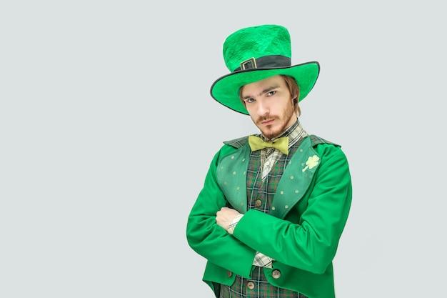 Hombre joven serio y molesto en traje verde. él cruzó las manos. pelirroja es infeliz. aislado en gris Foto Premium