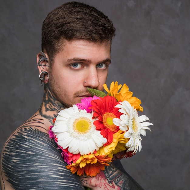 Hombre joven serio con orejas perforadas y nariz sosteniendo una flor de gerbera delante de su boca Foto gratis