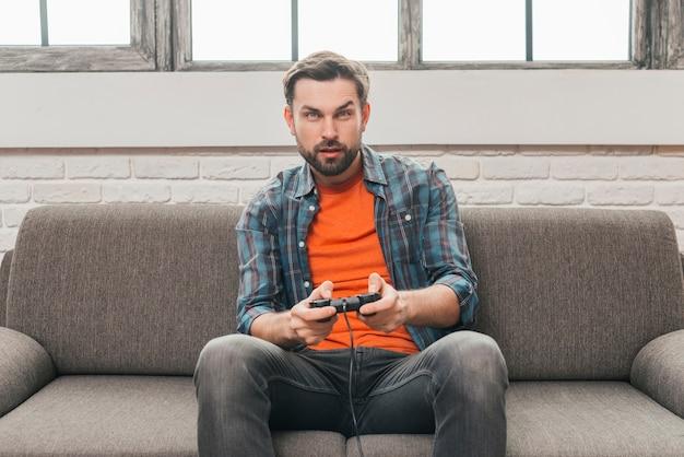 Hombre joven serio que se sienta en el sofá que juega al videojuego Foto gratis