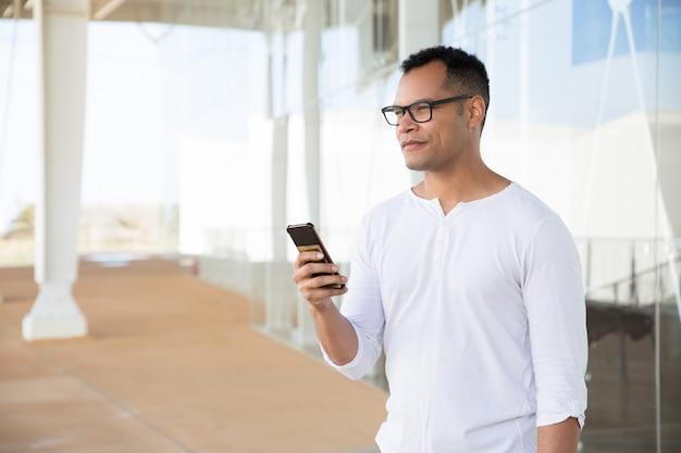 Hombre joven serio que sostiene el teléfono en las manos, mirando a un lado Foto gratis