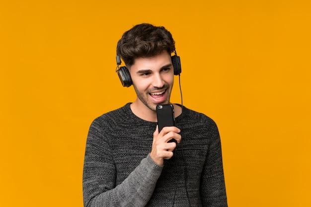 Hombre joven sobre aislado usando el móvil con auriculares y cantando Foto Premium