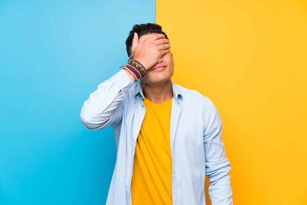 Hombre joven sobre ojos que cubren coloridos aislados por las manos Foto Premium
