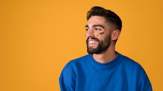 Hombre joven sonriente con el arco iris lgbt en la cara Foto gratis