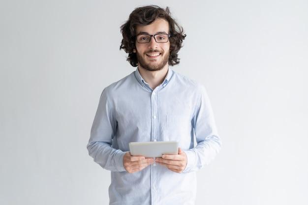 Hombre joven sonriente que coloca y que sostiene la tableta Foto gratis