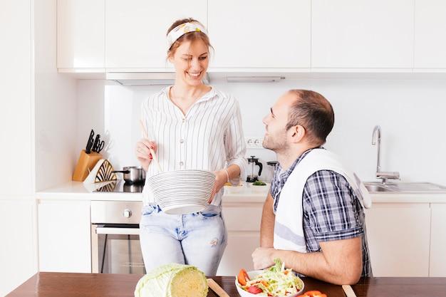Hombre joven sonriente que mira a su esposa que prepara la comida en la cocina Foto gratis