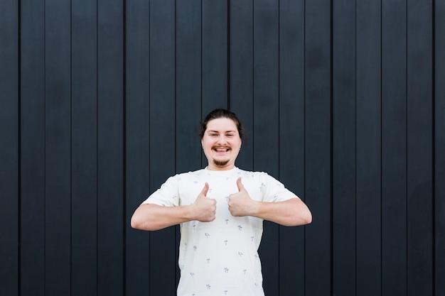 Hombre joven sonriente que se opone al contexto negro que muestra el pulgar encima de la muestra con dos fingeres Foto gratis