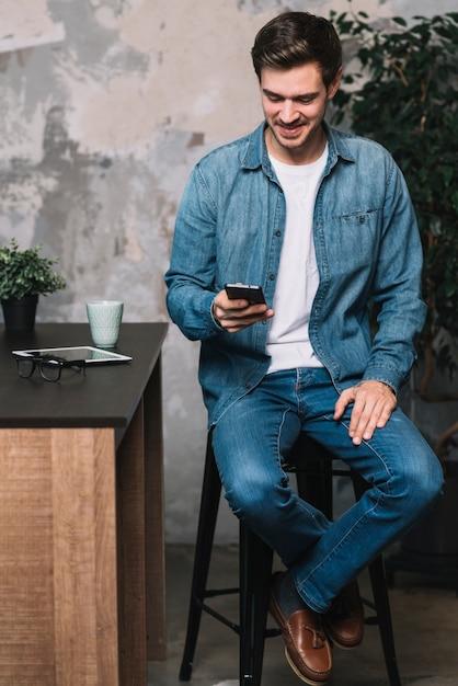 Hombre joven sonriente que se sienta en taburete usando el teléfono móvil en casa Foto gratis