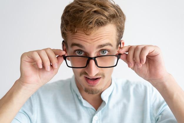 Hombre joven sorprendido que mira la cámara sobre los vidrios Foto gratis