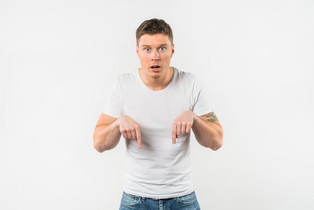 Hombre joven sorprendido que señala sus dedos hacia abajo contra el fondo blanco Foto gratis