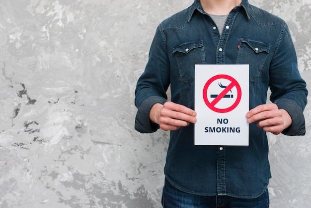 Hombre joven sosteniendo un cartel de texto y cartel de no fumar sobre la pared vieja Foto gratis