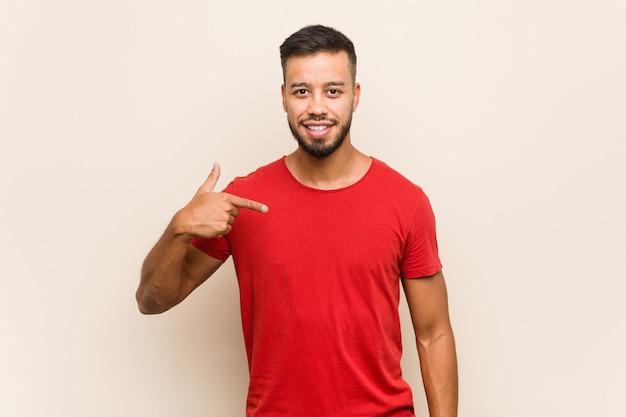 Hombre joven del sur de asia persona señalando con la mano a una camisa copia espacio, orgulloso y confiado Foto Premium