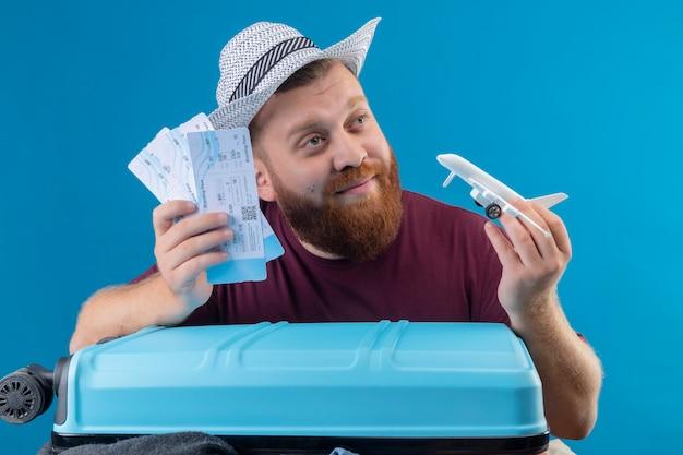 Hombre joven viajero barbudo con sombrero de verano con maleta llena de ropa con billetes de avión y avión de juguete juguetón optimista y feliz sonriendo mirando a un lado con mirada de ensueño sobre b Foto gratis