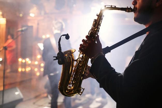 El hombre juega con un saxofón Foto gratis
