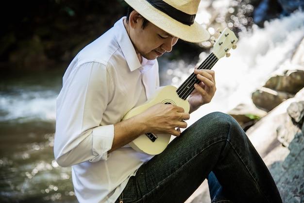 Hombre juega ukelele nuevo a la cascada. Foto gratis