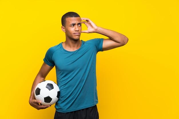 Hombre jugador de fútbol afroamericano que tiene dudas y con expresión de la cara confusa Foto Premium
