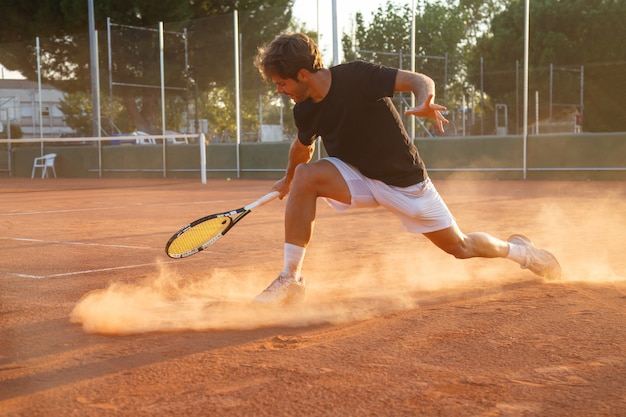 Hombre de jugador de tenis profesional jugando en la cancha en la tarde. Foto Premium