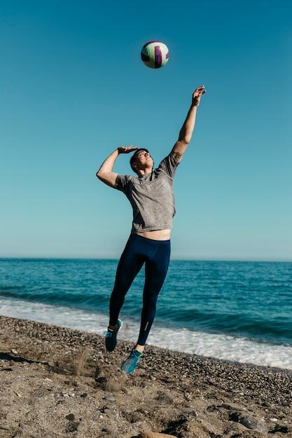 Hombre jugando al volleyball en la playa Foto gratis