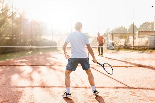 Hombre jugando tenis en la mañana a la luz del sol Foto Premium