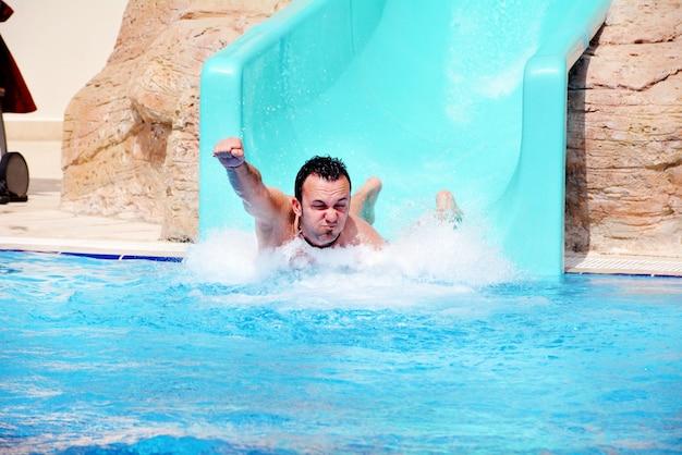 Hombre jugando en el tobogán de agua Foto gratis