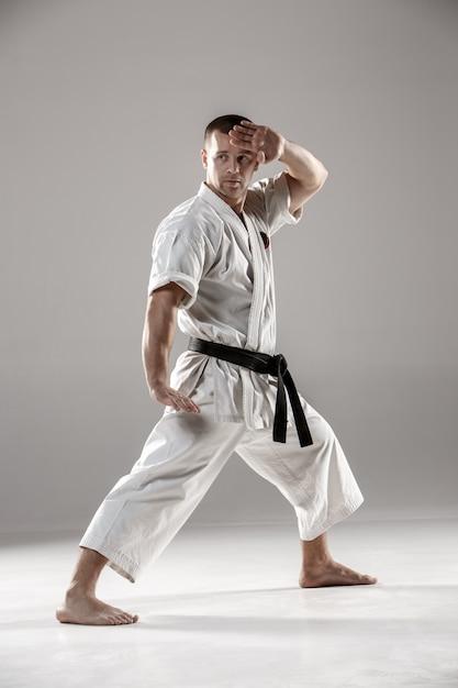 Hombre en kimono blanco entrenando karate Foto gratis