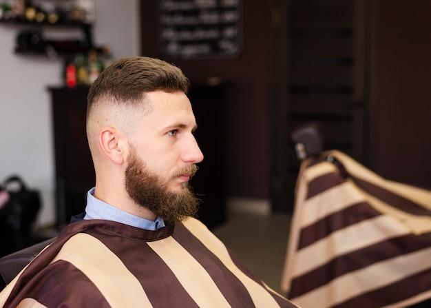 Hombre de lado esperando un nuevo corte de pelo Foto gratis