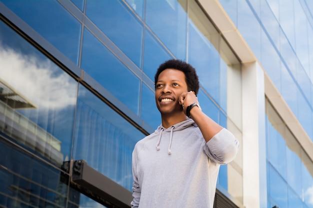 Hombre latino joven que habla en el teléfono móvil afuera. Foto Premium