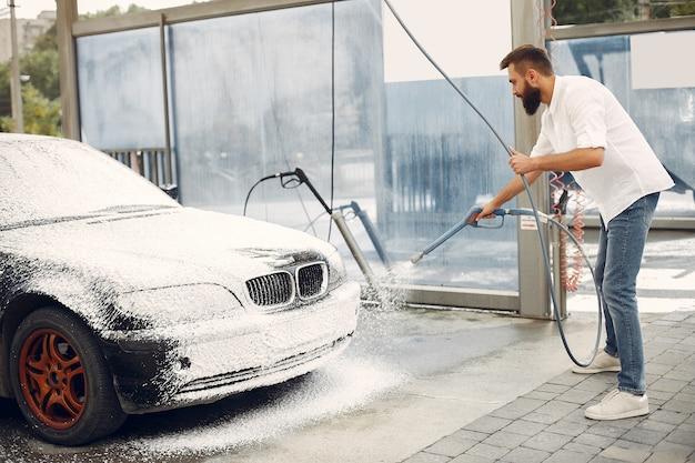 Hombre lavando su auto en una estación de lavado Foto gratis