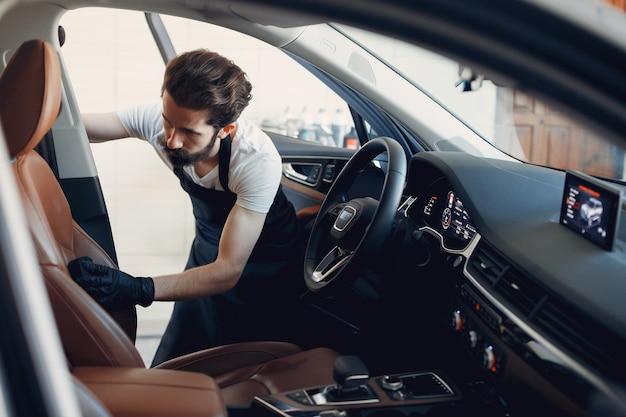 Hombre lavando su auto en un garaje Foto gratis