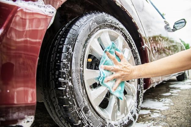 Hombre lavar el coche con champú Foto gratis