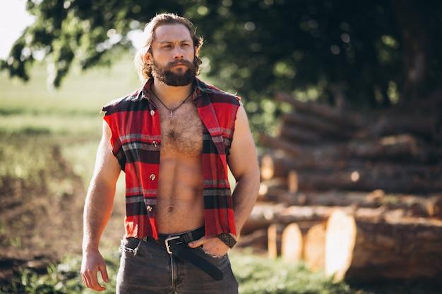 Hombre leñador en el bosque Foto gratis