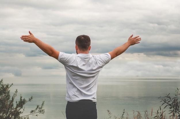 Hombre levantando los brazos junto a un lago Foto Premium