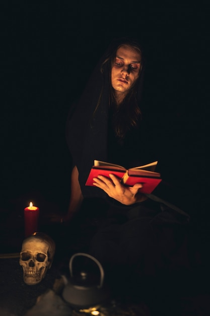 Hombre leyendo un libro de hechizos rojos en la oscuridad Foto gratis