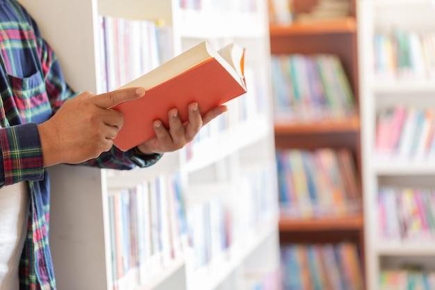 Hombre leyendo libro en sus manos en la biblioteca. Foto gratis