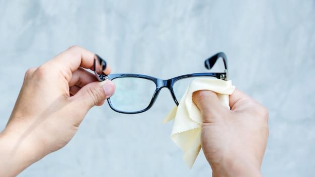 Hombre limpiando las gafas con tejido de microfibra. Foto Premium