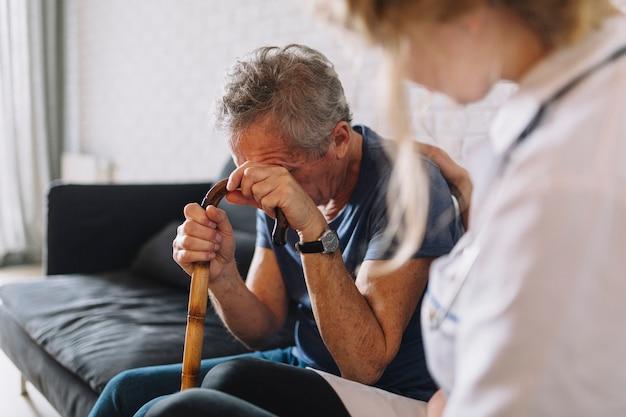 Hombre llorando en asilo de ancianos Foto gratis